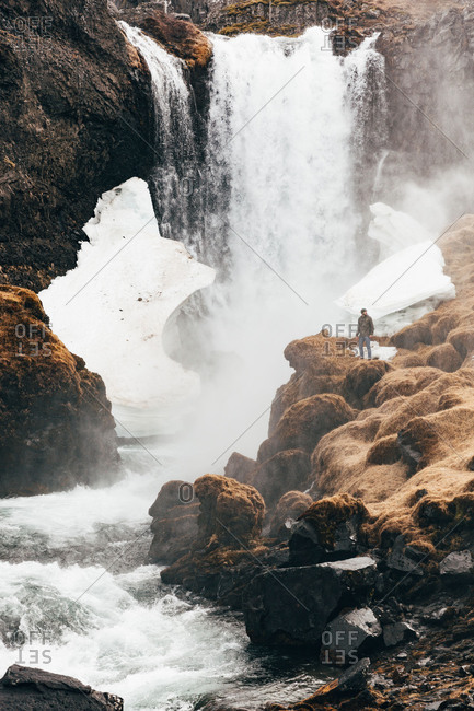 View at distance of man standing on rocky edge of hill with waterfall splashing on background, Iceland.