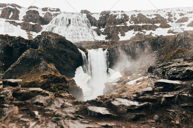Landscape of waterfall flowing among rocks and snow from high mountain in mist, Iceland.