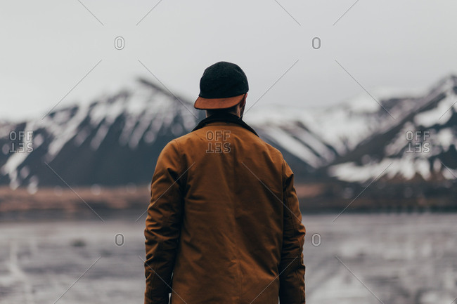 Back view of traveler in brown jacket and cap standing against cold mountains of Iceland.