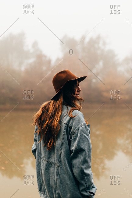 Pretty woman in hat at pond