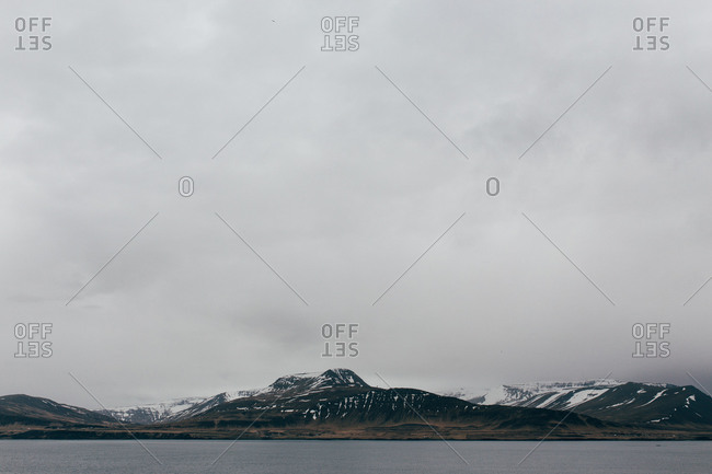 View of gloomy clouds above snowy range of mountains and lake water in Iceland.