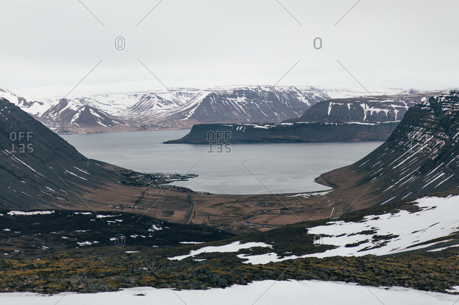 Aerial view of amazing land with snowy spacious terrain and mountains surrounding water in Iceland.