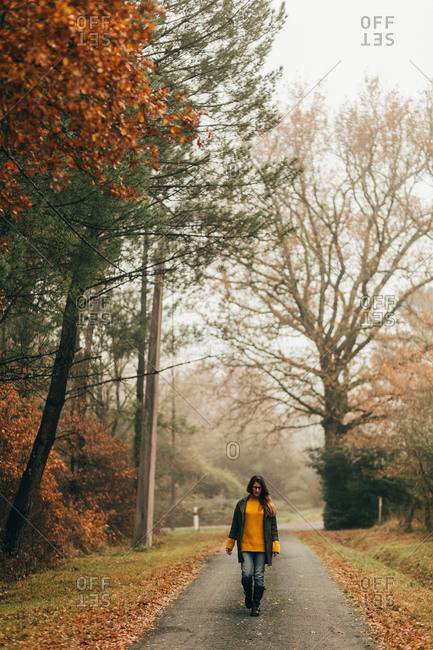 Pretty young woman walking on road in autumn woods.