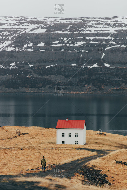 View of tourist walking on road towards small house placed alone on coast of cold lake in Iceland.