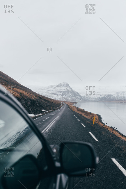 Black car driving down long road alongside cold lake with gloomy gray mountains on background in Iceland.