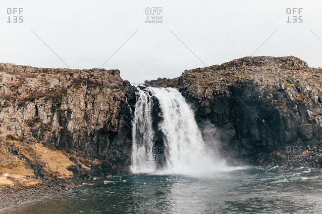 Landscape of beautiful Icelandic waterfall rushing down from rocky cliff making splashes in water.