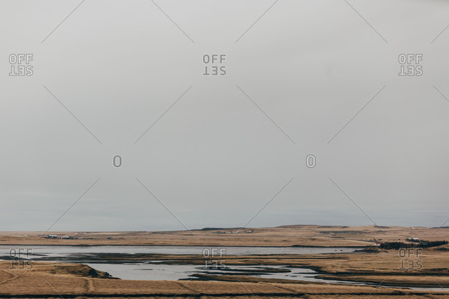 Panorama of amazing spacious plain with lakes under gray clouds in Iceland.