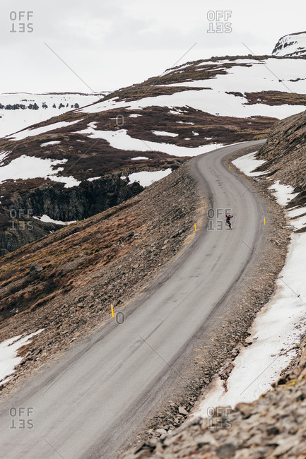 Aerial view of traveler riding skate on long remote road in snowy mountains of Iceland.