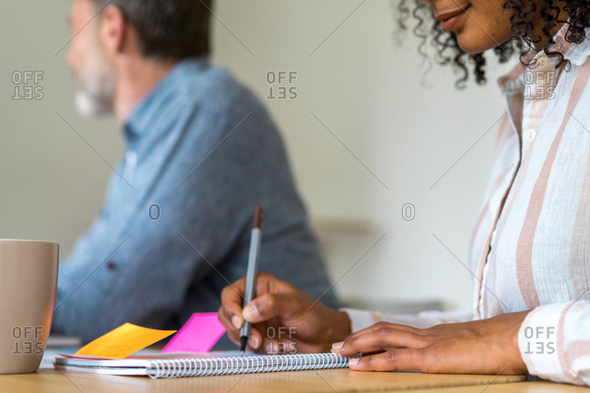 Worker sitting with colleague in office and writing in notebook