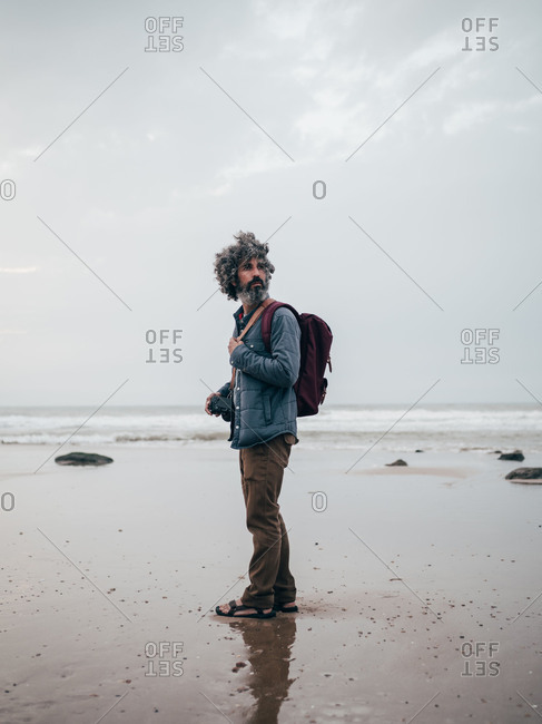 Tourist standing at calm ocean
