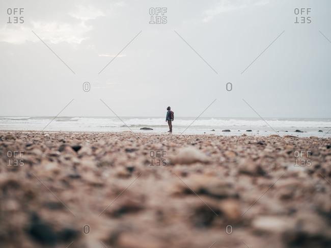 Tourist standing at calm ocean