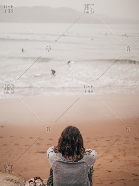 Woman looking at surfers in sea