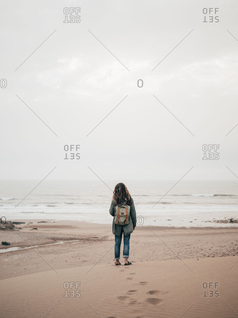 Woman with backpack at ocean