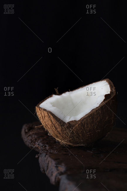 Close-up of ripe aromatic coconut half on rough wooden table against black background.