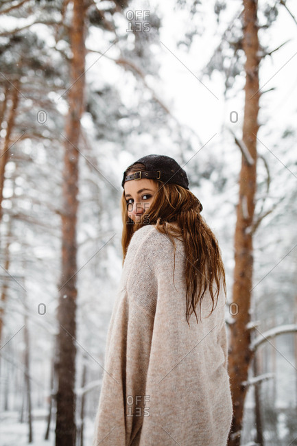 Young pretty woman standing in winter forest and looking back at camera.