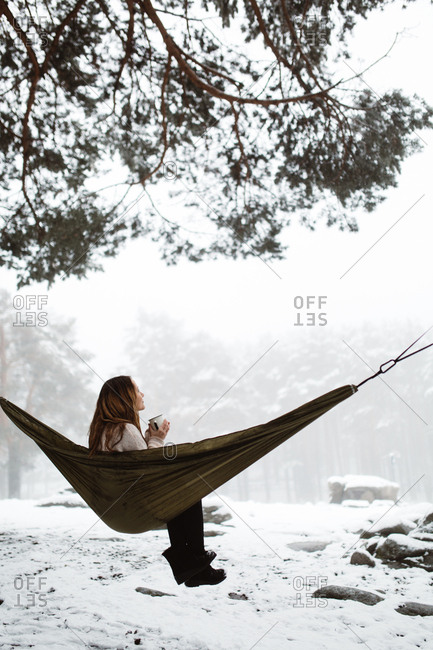 Side view of pretty dreamy young woman sitting in hammock and having hot drink in winter nature.