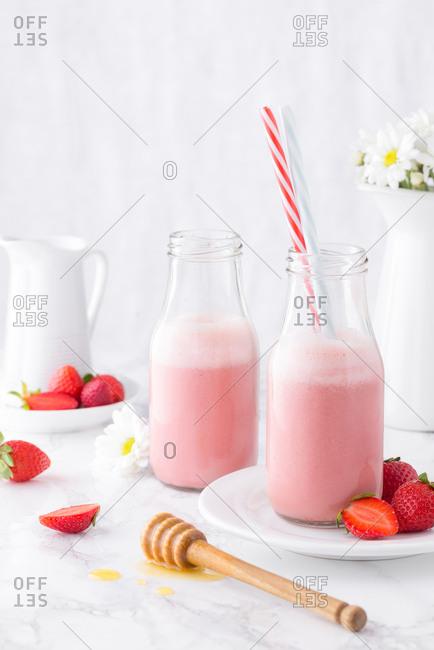 Pink strawberry milkshake served in bottles with straw.