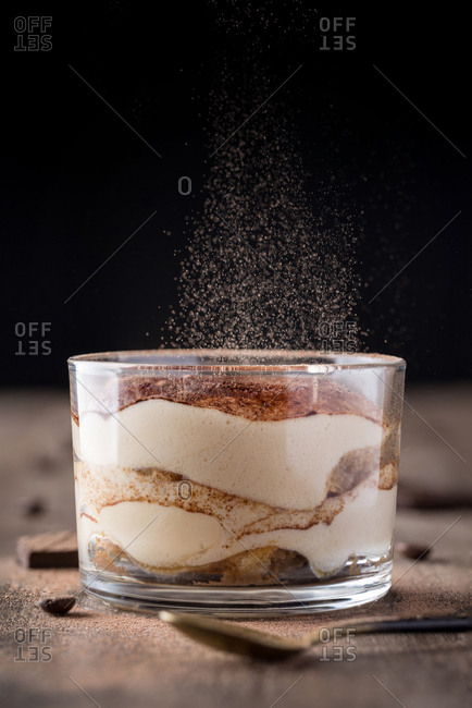 Close-up of fresh tiramisu dessert in glass with particles of cocoa dust falling on top.