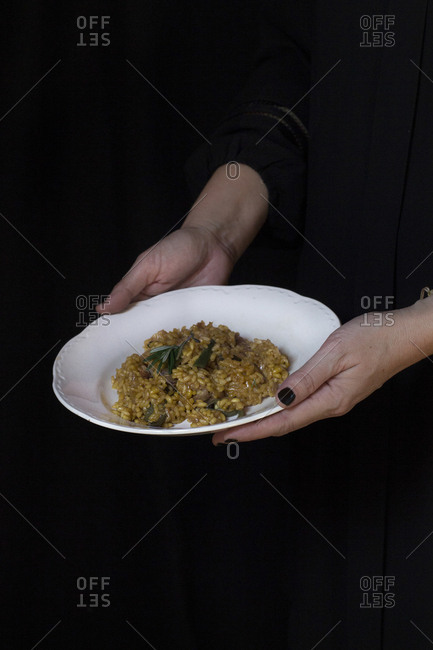 Hands of unrecognizable cook holding plate with risotto.
