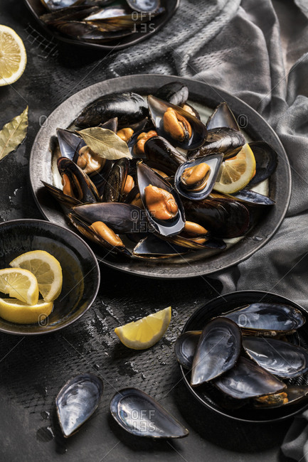 From above bowl of tasty baked mussels served with lemon.