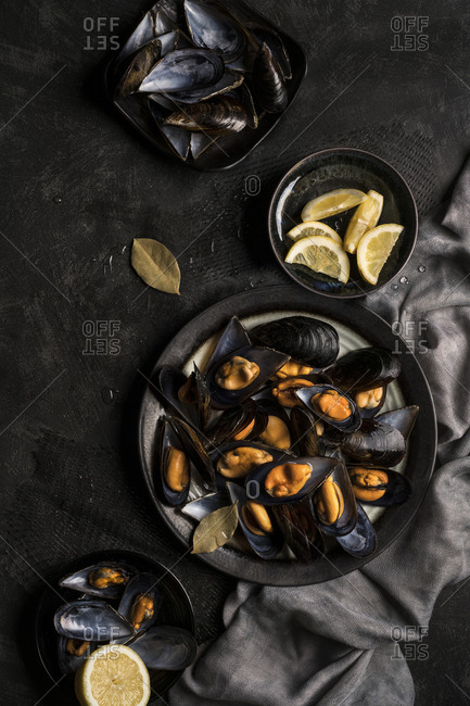 Top view of fresh baked appetizing mussels served with lemon on dark table.