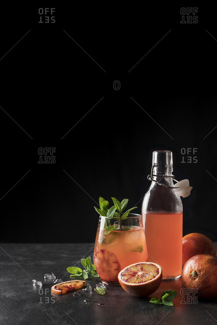 Jug and bottle filled with refreshing lemonade made of red oranges.
