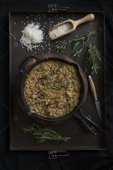 From above risotto with spices and rosemary on a pan.