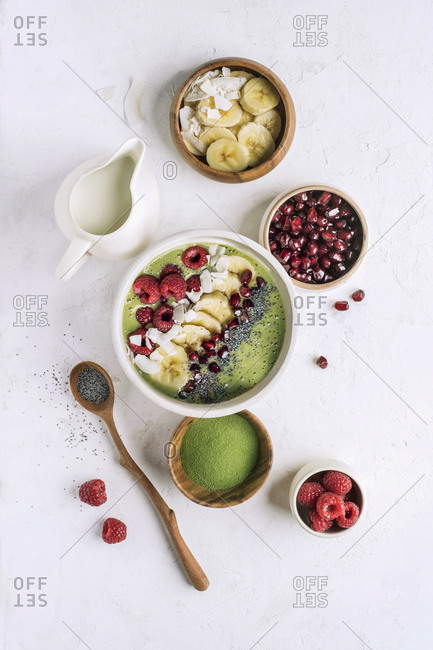Flat lay of bowl with healthy smoothie for breakfast in composition with various additives as fruit and matcha powder.
