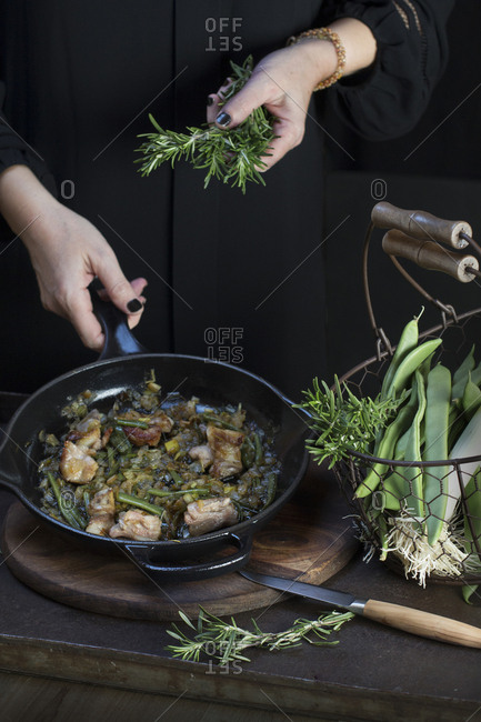 Crop unrecognizable cook putting rosemary to pan with cooking food.