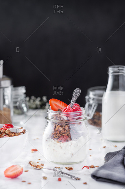 Glass jar with tasty nutrient breakfast with granola, cream, and strawberry.