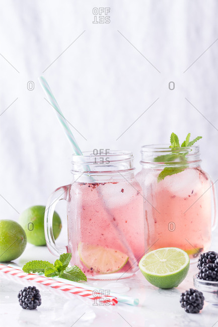 Two drinking jars with refreshing lemonade containing lime and blackberry.