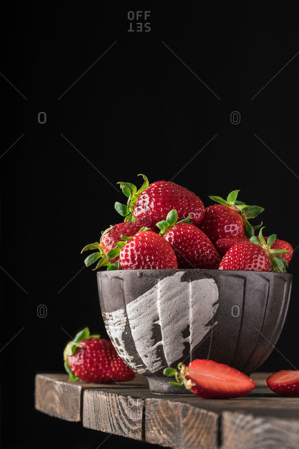 Close-up of red ripe strawberries arranged in gray craft bowl on wooden table against black.