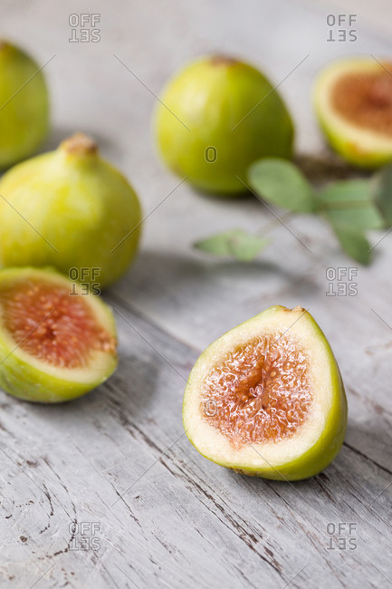 Close-up green unripe fig fruit on wooden table.