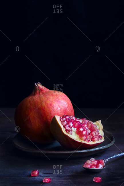 Tasty opened and whole pomegranate on spoon on dark background.