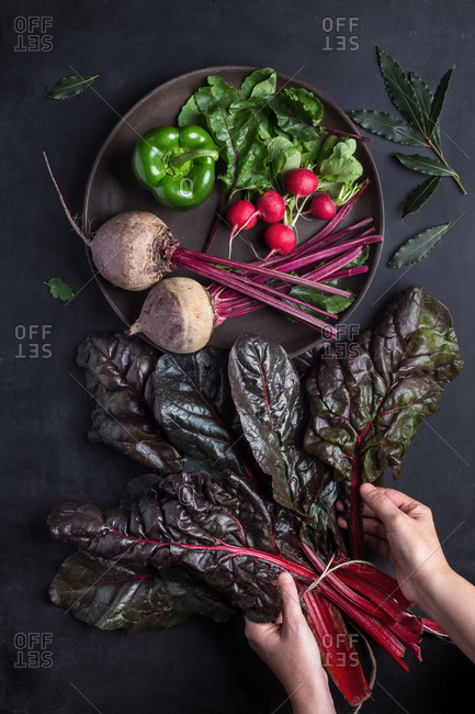 From above hands taking out beetroot leaves from the bunch.