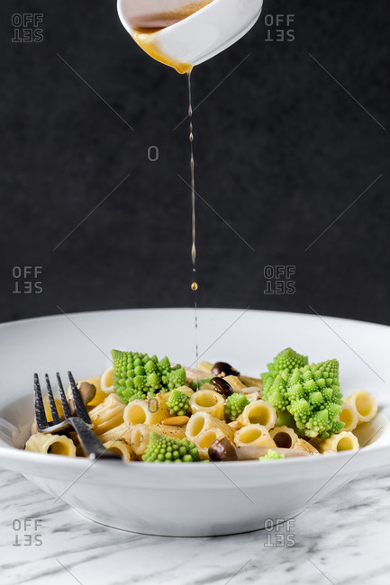 Sauce pouring to appetizing pasta with romanesco cauliflower.