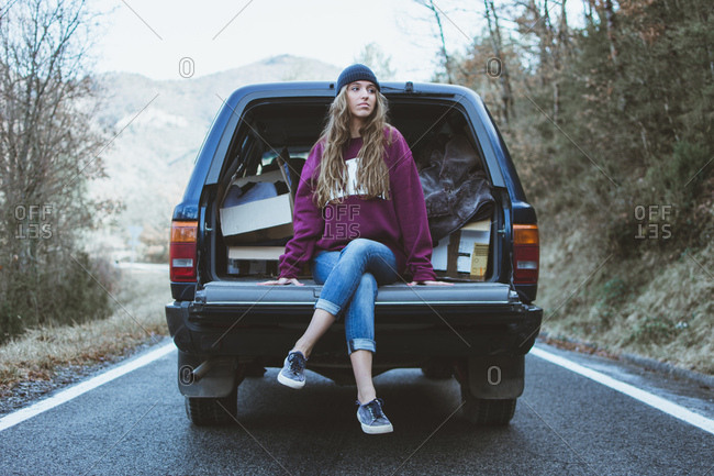 Young thoughtful woman sitting on trunk of a car in the forest.