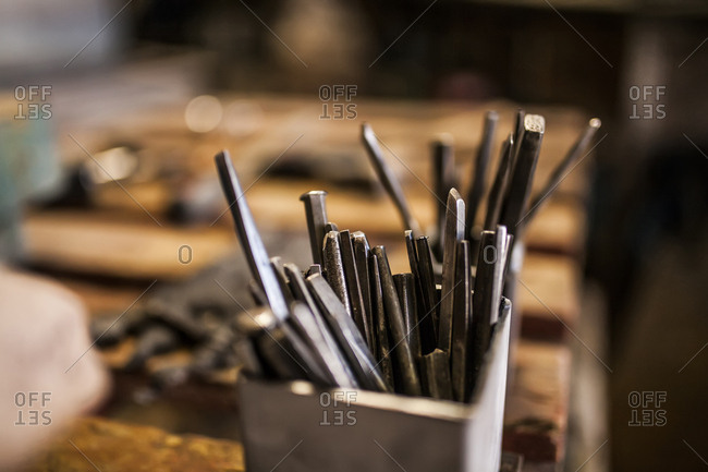 Crop view of hammer and instruments on wooden metallurgical table