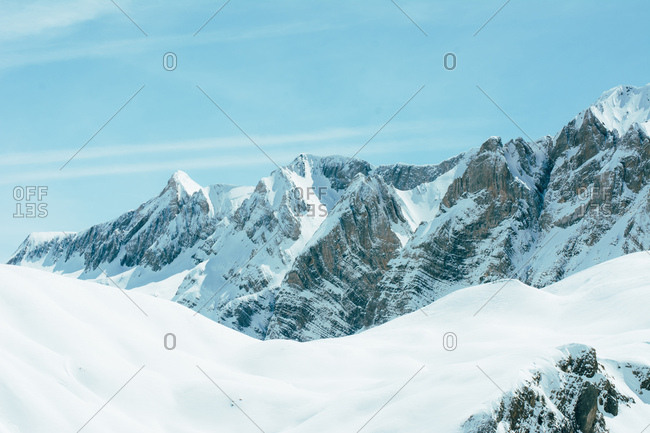 Beautiful view to snowy white mountains under blue sky in sunny day.