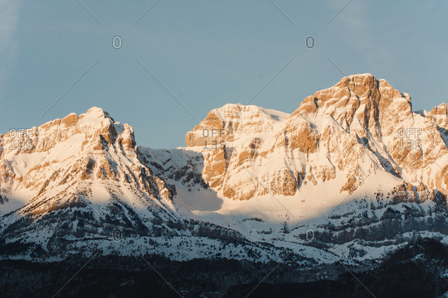 Picturesque view to white snowy mountains with sun flare in nature.