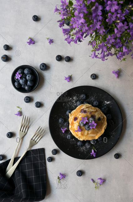 Stack of appetizing tasty crumpets with blueberry and purple flowers decoration on a table