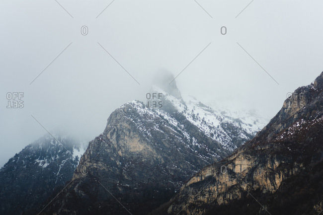 Picturesque peaks covered with snow in foggy day.