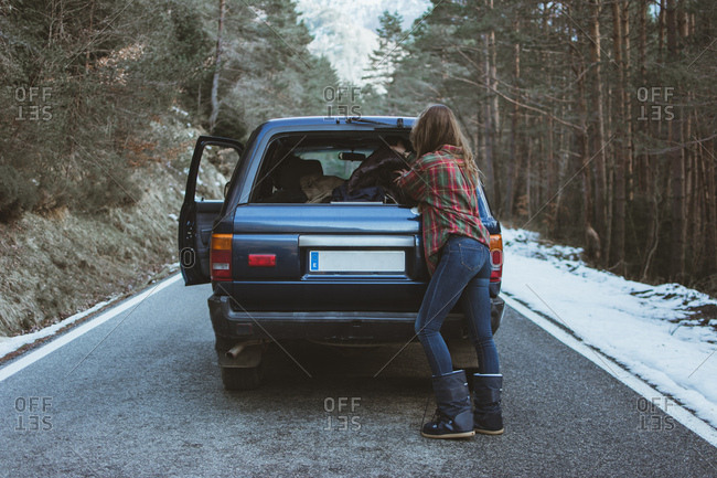 Back view of woman packing stuff to trunk of the car on road in winter forest.