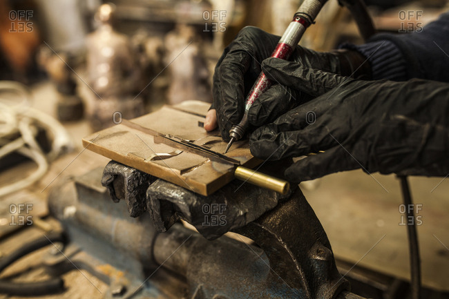 Crop view of hands in black rubber gloves working by equipment on details on carpenter machine tool