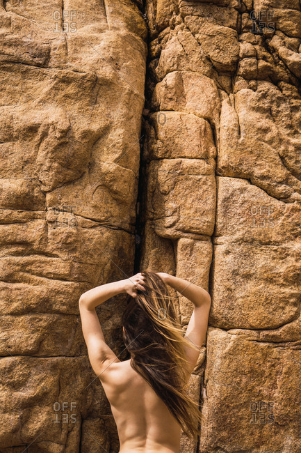 Back view of naked woman climbing up on rough mountain wall.