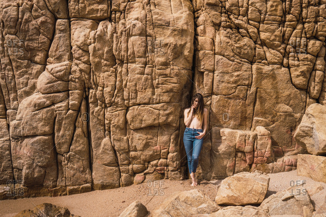 Topless attractive young woman in jeans standing and posing at the rough rock.