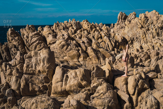 Side view of unrecognizable attractive nude woman standing on rock in sunny day.