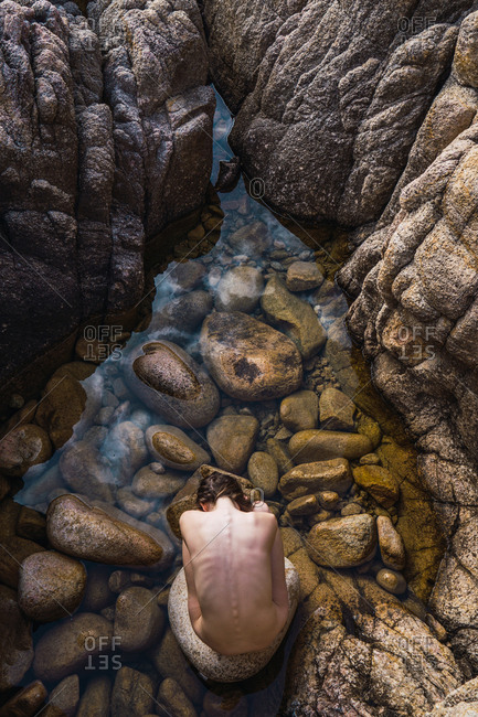 Top view of nude woman sitting on stones and touching back in the water in nature.