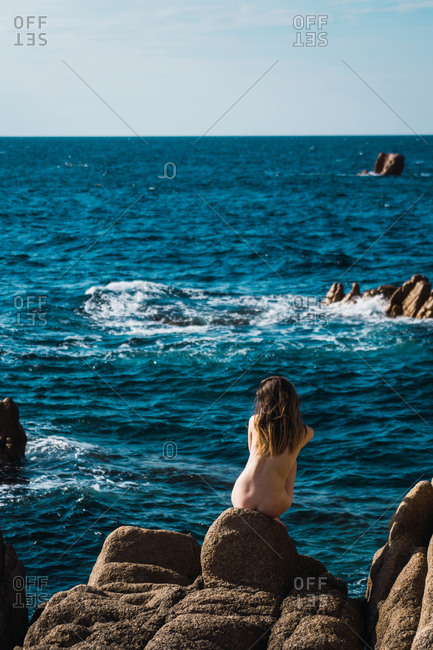 Back view of attractive naked woman sitting on stone at blue ocean.