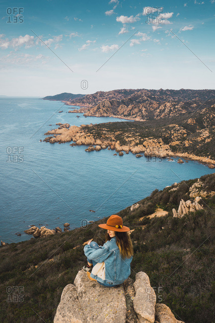 Pretty woman in hat sitting on the rock edge on background of woods and the ocean.